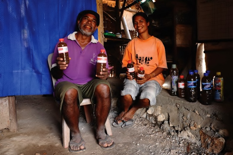 Bernadus missa and his wife holding the bio-slurry inside their humble home. Photo: Sonang Elyas/BIRU