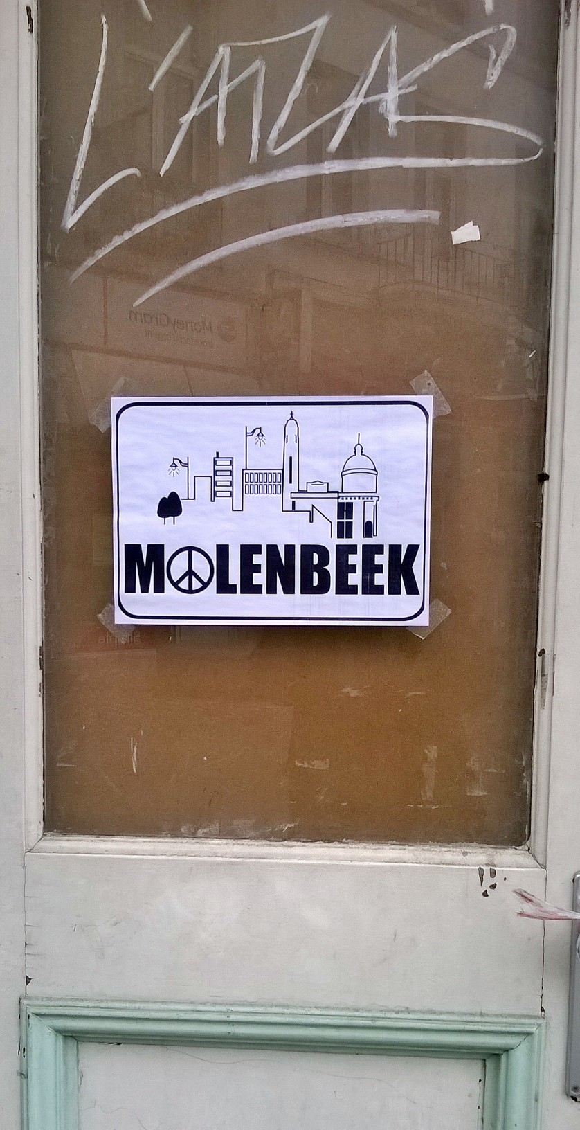 df5d4eb79bc302 A signane of Molenbeek and the peace symbol posted on the window of a  building in